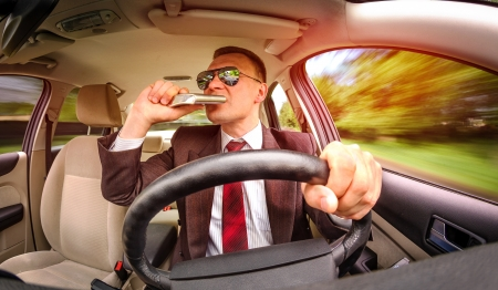 Drunk man in a suit and sunglasses driving on a road in the car vehicle. photo