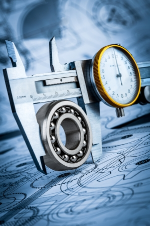 Metal vernier caliper and Ball bearings on technical drawing a blue toning Stock Photo