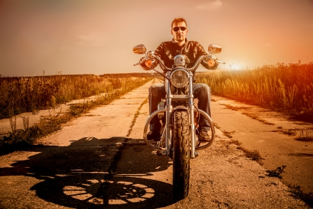 Biker man wearing a leather jacket and sunglasses sitting on his motorcycle looking at the sunset. Zdjęcie Seryjne
