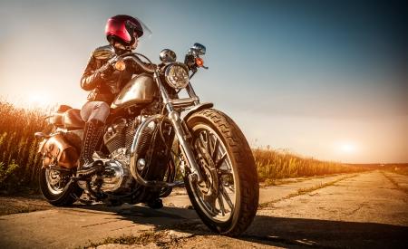 Biker meisje op een motorfiets in een leren jas en een helm, kijkt naar de manier waarop