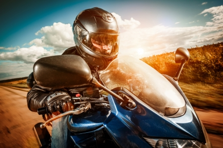 Biker in helmet and leather jacket racing on the road photo