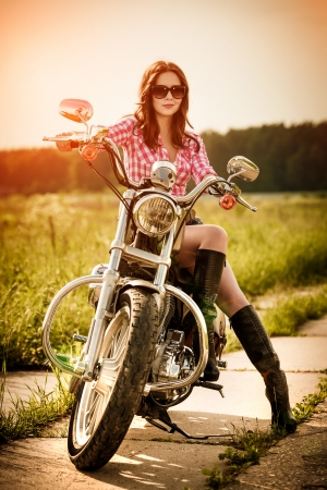 Biker girl with sunglasses and motorcycle photo