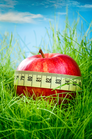 Red apple and measuring tape on the green grass. photo
