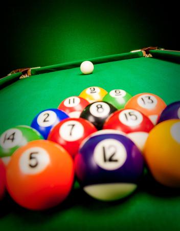 Fifteen billiard spheres lay on green cloth photo