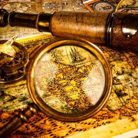 Vintage magnifying glass, compass, telescope and a pocket watch lying on an old map. photo