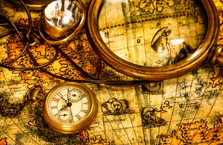 bygone: Vintage magnifying glass, compass, telescope and a pocket watch lying on an old map.