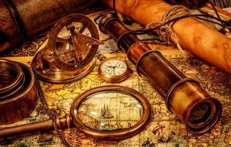 Vintage vergrootglas, kompas, verrekijker en een zakhorloge liggend op een oude kaart.
