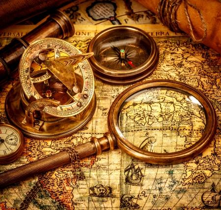 ビンテージ虫眼鏡、コンパス、望遠鏡と懐中時計、古い地図の上に横たわる。