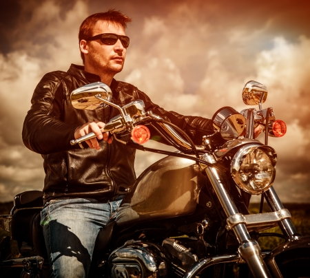 Biker man wearing a leather jacket and sunglasses sitting on his motorcycle looking at the sunset. Stock Photo