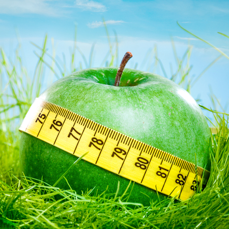 Green apple and measuring tape on the green grass. photo