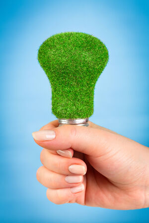 overuse: Eco light bulb in hand on blue background Stock Photo