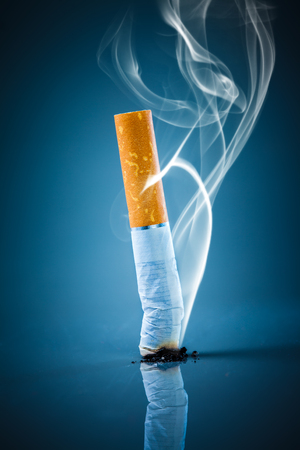 vices: No smoking. Cigarette butt on a blue background. Stock Photo