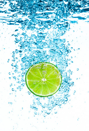 falling water: Fresh green lime in the clear water on white background.