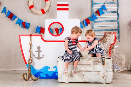 kids room: Two little girls play with seashells, sea theme. Stock Photo
