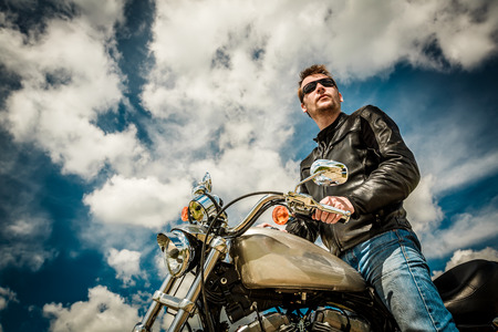 석양을보고 가죽 재킷과 자신의 오토바이에 앉아 선글라스를 착용하는 바이커 남자. 스톡 콘텐츠