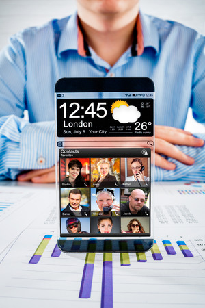Futuristic Smart phone (phablet) with a transparent display in human hands. Concept actual future innovative ideas and best technologies humanity. photo