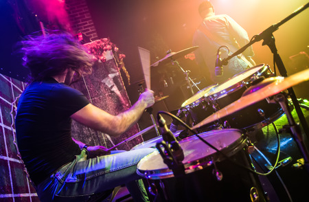 bass drum: Drummer (blurred motion) playing on drum set on stage. Focus on the drum and microphone. Stock Photo