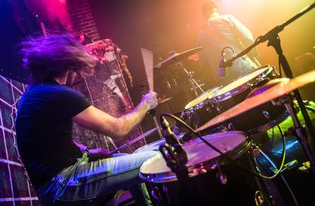 tambor: Drummer (movimiento borrosa) jugando en batería en el escenario. Centrarse en la batería y el micrófono.