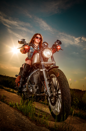 rebel: Biker girl with sunglasses sitting on motorcycle