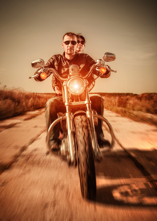Couple Bikers in a leather jacket riding a motorcycle on the road photo