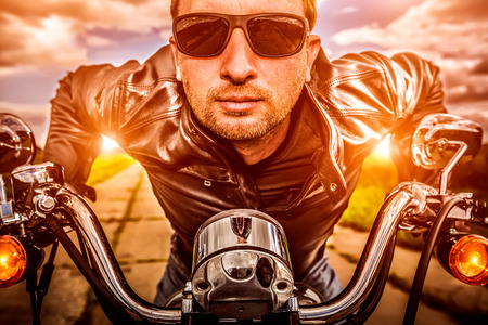 Biker man wearing a leather jacket and sunglasses sitting on his motorcycle looking at the sunset. Filter applied in post-production. Stock Photo
