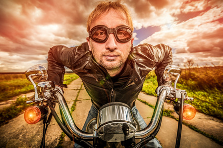 Funny Biker in sunglasses and leather jacket racing on the road (fisheye lens). Filter applied in post-production. photo