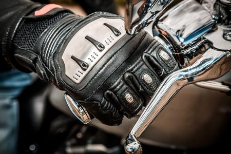 motociclista: La mano del hombre en una motocicleta que compite con guantes tiene un control del acelerador de motocicleta. Protección de las manos de las caídas y accidentes.