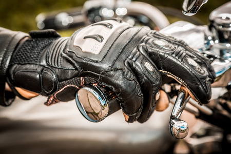 motorcycle accidents: Human hand in a Motorcycle Racing Gloves holds a motorcycle throttle control. Hand protection from falls and accidents.