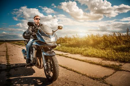 Hombre del motorista que llevaba una chaqueta de cuero y gafas de sol sentado en su moto mirando el atardecer.