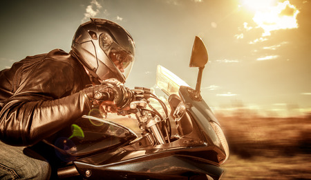 Motorista en el casco y la chaqueta de cuero de carreras en la carretera. Filtro aplicado en post-producción. Foto de archivo