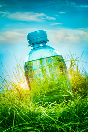 energy drinks: Bottle of water on the green grass Stock Photo