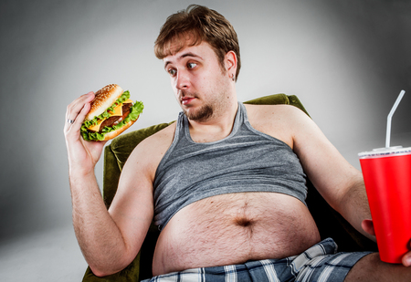 eating fast food: Fat man eating hamburger seated on armchair. Style fast food. Stock Photo