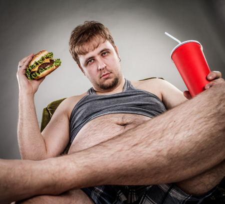 big belly: Fat man eating hamburger seated on armchair. Style fast food. Stock Photo
