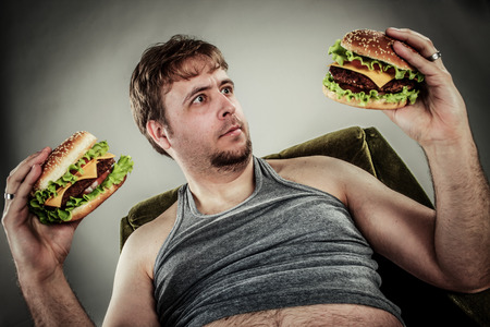 Fat man eating hamburger seated on armchair. Style fast food. Stock Photo