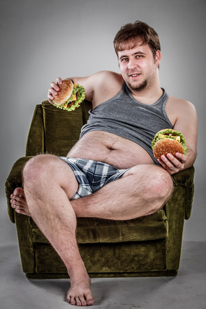 ugly people: Fat man eating hamburger seated on armchair. Style fast food. Stock Photo