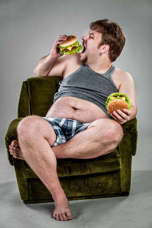 Fat man eating hamburger seated on armchair. Style fast food. photo