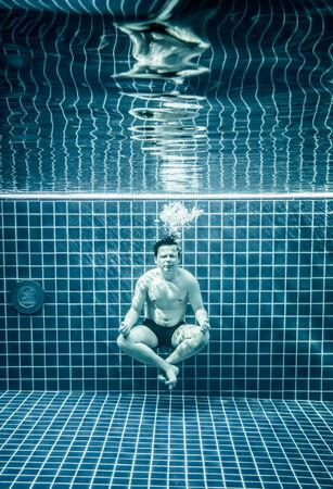dhyana: L'uomo sotto l'acqua in una piscina per rilassarsi nella posizione del loto