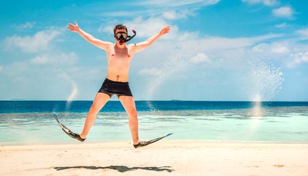 flippers: Hombre divertido que salta en aletas y m�scara. Vacaciones de vacaciones en una playa tropical en las Islas Maldivas. Foto de archivo