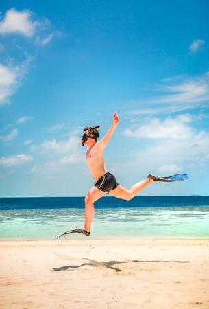 flippers: Hombre divertido que salta en aletas y máscara. Vacaciones de vacaciones en una playa tropical en las Islas Maldivas. Foto de archivo