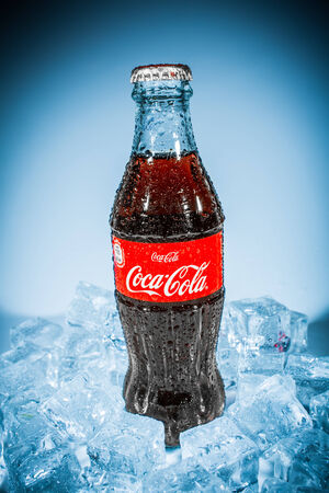 MOSCOW, RUSSIA-APRIL 4, 2014: Bottle of Coca-Cola on ice. Coca-Cola is a carbonated soft drink sold in stores, restaurants, and vending machines throughout the world.