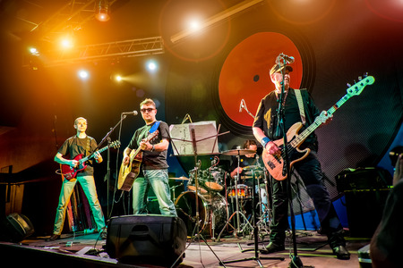 performs: Band performs on stage, rock music concert in a nightclub