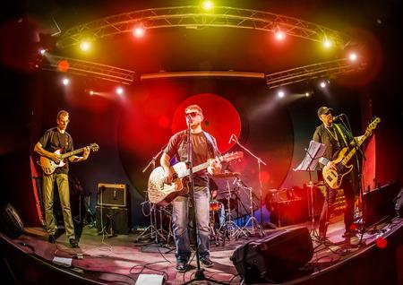 concierto de rock: Band actúa en el escenario, el concierto de música de rock en una discoteca Foto de archivo