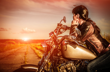 Biker girl in a leather jacket on a motorcycle looking at the sunset. photo