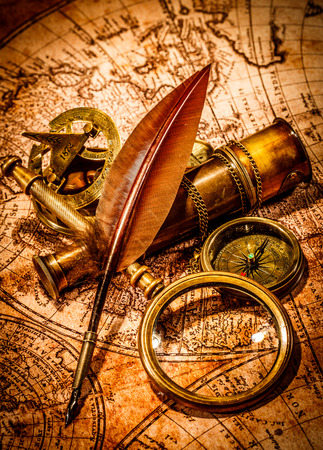 antiquity: Vintage magnifying glass, compass, goose quill pen and spyglass lying on an old map.
