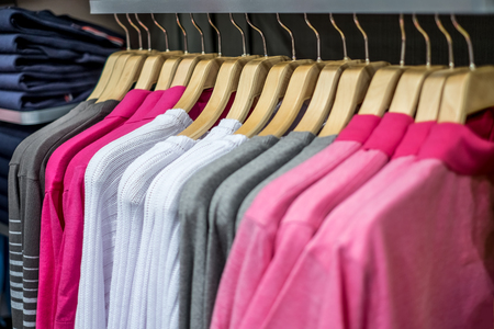 clothing rack: Fashionable clothing on hangers in shop