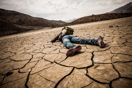 erosion: traveller lays on the dried ground