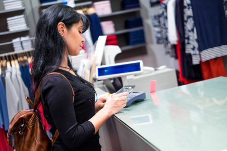 contactless: Girl pays to shop using mobile phone. NFC - Near field Communication. Mobile payment. Stock Photo