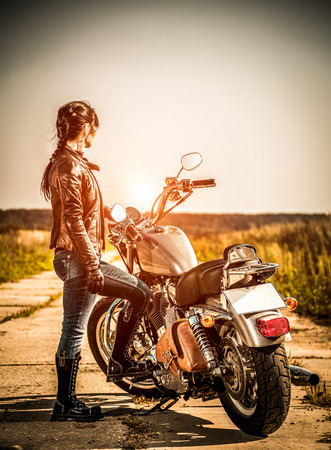 Biker girl stands on the road and looks into the distance photo