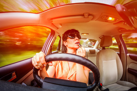 inattentive: Women make up lips at the wheel the car, not stares on the road creating an emergency situation.