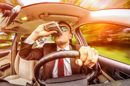 borracho: Hombre borracho en un traje y gafas de sol de conducción en una carretera en el vehículo.